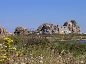 Eine Insel mit zwei Felsengruppen, dazwischen ein kleines Haus