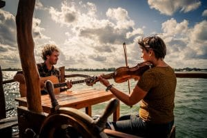 """Florian und Anouk sitzen für ihr Album """"Port de Taipana"""" mit Gitarre und Violine auf der sonnenbeschienenen Veranda ihres Hausbootes."""
