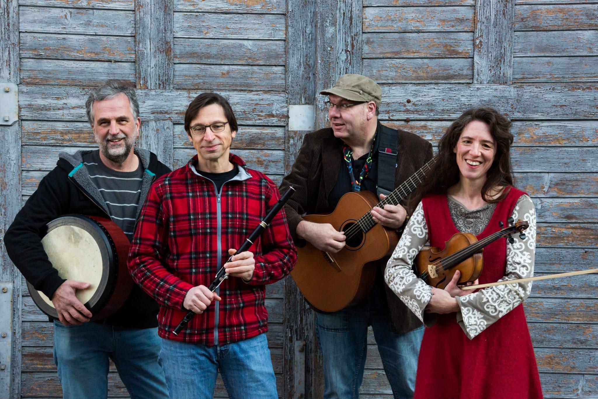 Die vier Personen Band Colludie Stone stehen mit Ihren Musikinstrumenten vor einer Holzwand