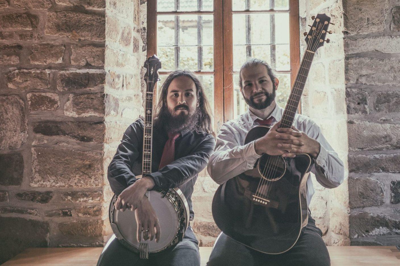 Duo STOUT steht mit Banjo und Gitarre vor einem Gewölbefenster